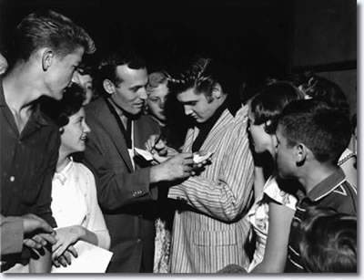 Carl Perkins and Elvis Presley sign autographs at Overton Park Shell on the night of June 1, 1956. Some 5,000 teenagers turned out that night for two hours of rock and roll by various artists including Perkins. Elvis Presley made a surprise appearance at the show, but did not perform.