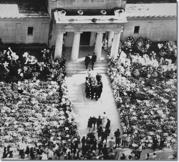 More than 3,100 floral sprays cover the lawn outside the mausoleum at Forest Hill Cemetery, where pall bearers deliver Presley's casket Aug. 18, 1977.