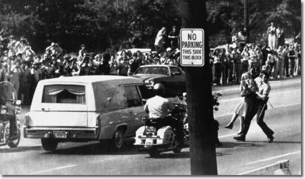 A Memphis policeman carries away a young woman trying to reach the hearse bearing the body of rock and roll star Elvis Presley during the funeral procession to Forest Hill Cemetery on Aug. 18, 1977. Thousands lined the route for the final farewell.