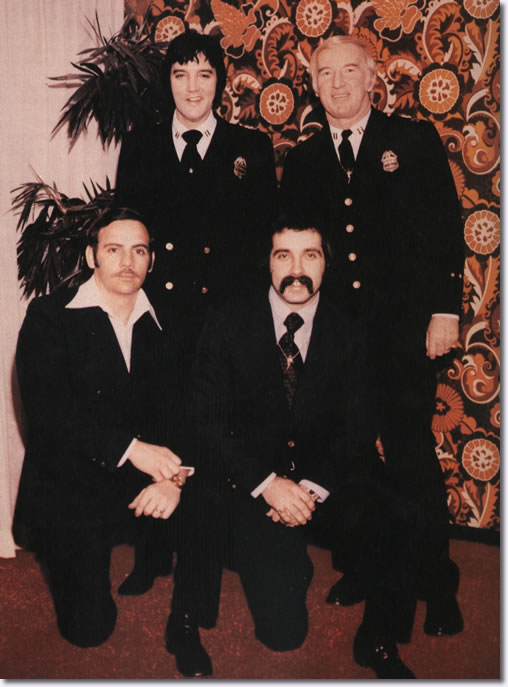 Elvis in Denver Police uniform with (standing right) Denver Police Capt. Jerry Kennedy and (kneeling, left to right) officers Bob Cantwell and Ron Pietrafeso, January 1976.