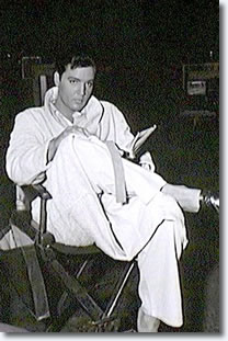 Elvis in his robe relaxing and reading in between scenes.