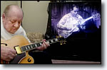 Hank Garland plays his guitar in his Orange Park home to a video clip of one of his 1950's vintage performances.