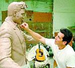Artist Eric Kaposta works on a statue of Elvis.