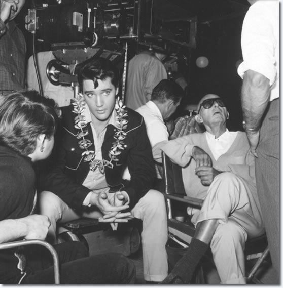 Elvis on the set of the 1965 film, Tickle Me. The photo captures Elvis resting between filming scenes with the cast and crew. For his work on the film, Elvis received $750,000, which was more than half of the budget for Tickle Me. He also received 50% of the film's profits.