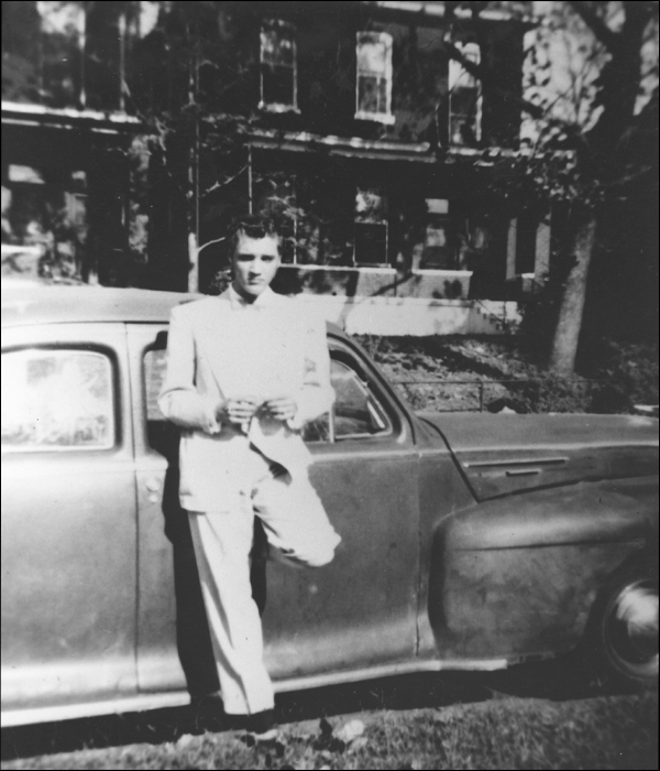 Elvis poses near the family''s Lincoln in front of his home at 462 Alabama.