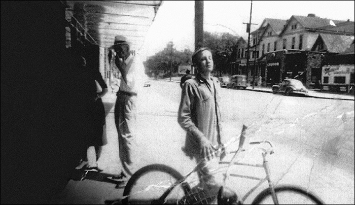 A young Elvis posing on his bike in front of the S&S Drug Store in 1949.