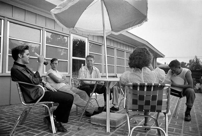 Taking a break from fans, Elvis relaxed with family on the patio of his home at 1034 Audubon Drive in Memphis. Elvis paid $40,000 for the four-bedroom, ranch-style house in 1956, a year before he puchased Graceland. On the same day this photograph was taken, July 4, Elvis also played a benefit concert at Russwood Park.