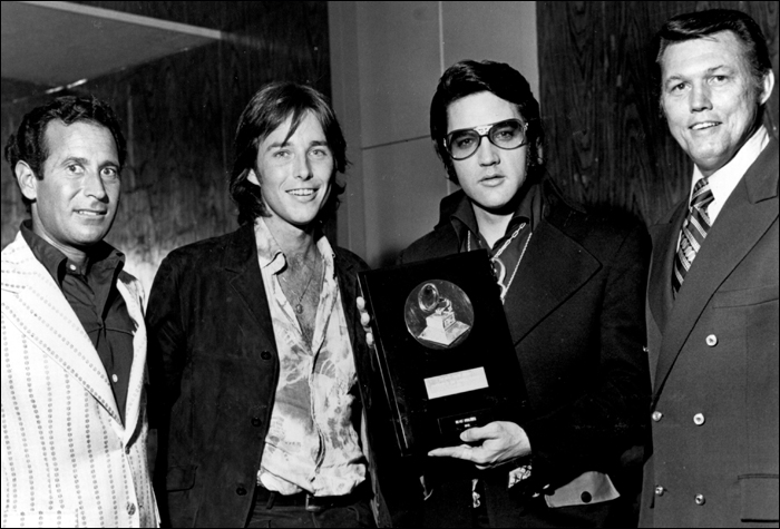 On August 28, 1971, Elvis received the Lifetime Achievement Award from, left to right, NARAS official Gene Merlin, Bing Crosby's nephew Chris Crosby and Bill Cole. This photo was taken in Elvis' dressing room in Las Vegas.