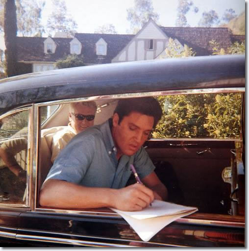 Elvis Presley signing an autograph, circa 1966-1967. Vernon Presley can be seen sitting behind Elvis.