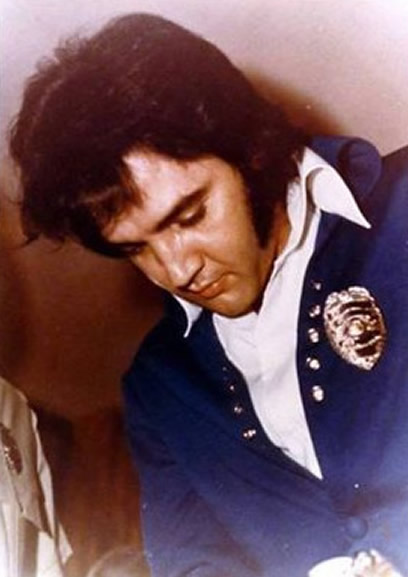 Elvis Presley wearing a police badge.