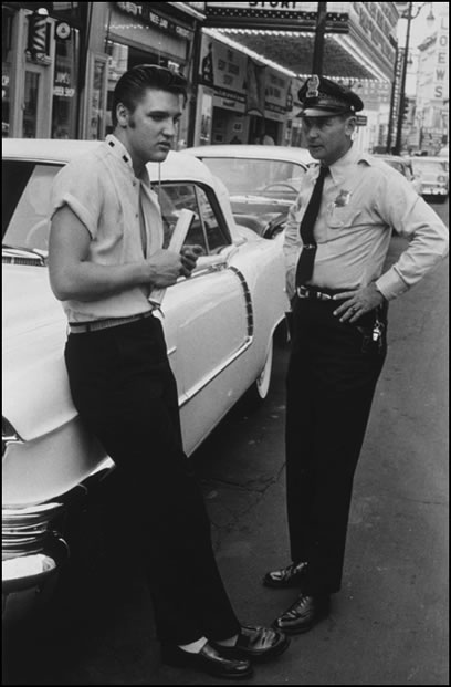 Elvis was friends with members of the Memphis Police Department before he became famous. Here he chats with an officer before getting a haircut at Jim's Barber Shop on Main Street.