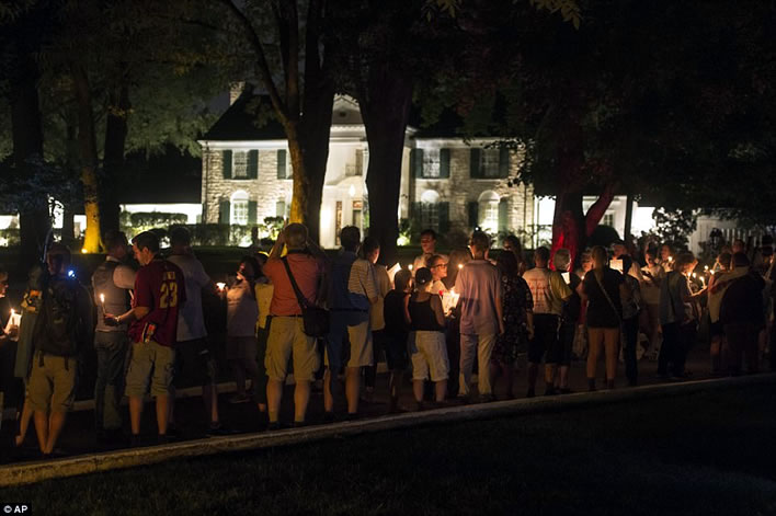 Memorial: Visitors are seen here taking part in the vigil outside the Graceland mansion, where Elvis died of a heart attack some 40 years ago.