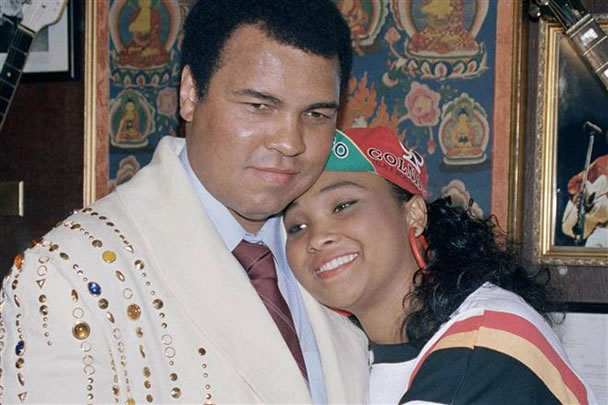 "Former heavyweight champion Muhammad Ali gets a hug from his daughter Maryum ""May May"" Ali at New York's Hard Rock Cafe May 12, 1988. Ali donated the robe he's wearing, given to him by Elvis Presley and worn at many of his title fights, to a display of memorabilia at the club. (AP Photo/Richard Drew)"